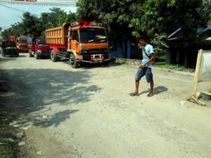 SEORANG pemuda melintas diantara antrian truk pasir.